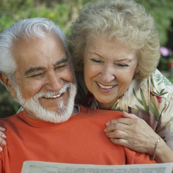 happy-senior-couple-reading-newspaper-together